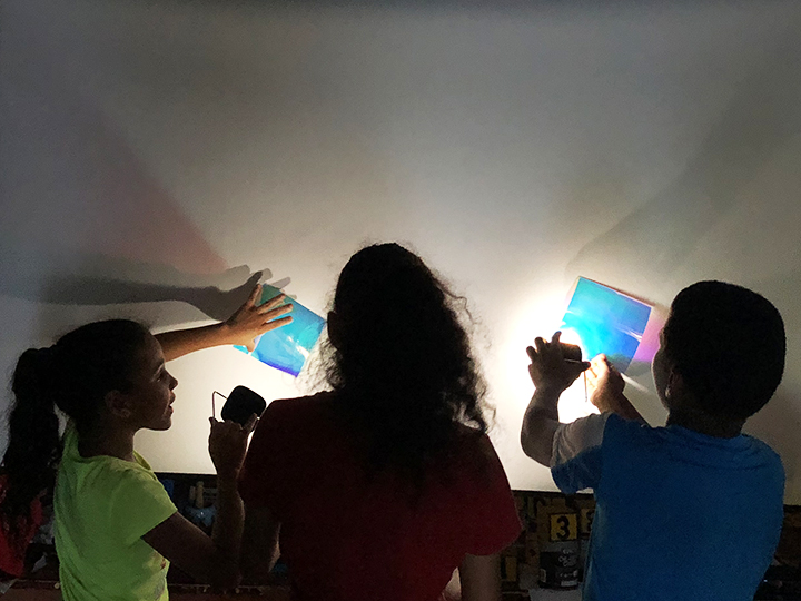 three kids experimenting with portable lights