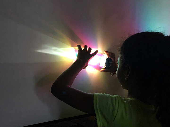 little girl experimenting with a portable light