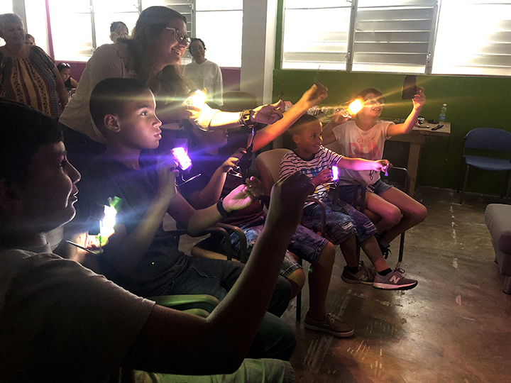 volunteer leading children in a lighting workshop