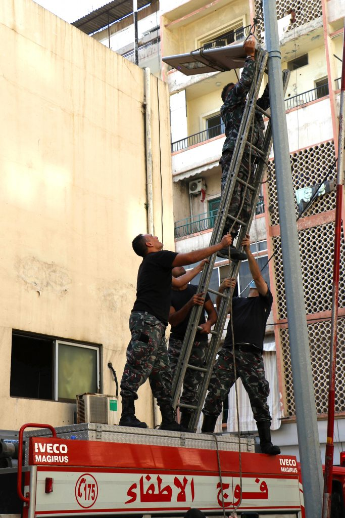 firefighters installing a streetlight we donated to them