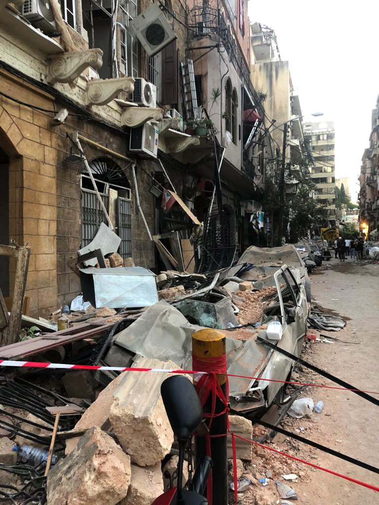 street and cars covered in rubble with blown out windows and dangling air conditioners