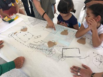 residents looking at a hand drawn map of their playground to determine where to install lights