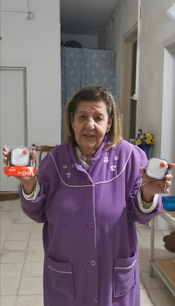 a lady smiles holding up two portable lanterns we donated to her