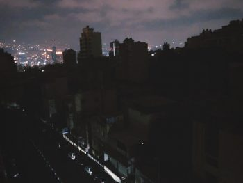 a dark neighborhood in beirut with lights visible in the distance